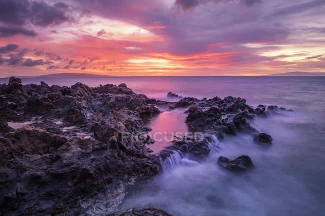 Pôr-do-sol dramático sobre o oceano com cachoeiras ao longo da costa acidentada; Wailea, Maui, Havaí, Estados Unidos da América — Fotografia de Stock