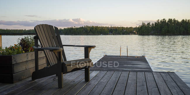 A wooden Adirondack chair sits on a dock on a tranquil lake at sunset; Lake of the Woods, Ontario, Canada — Stock Photo
