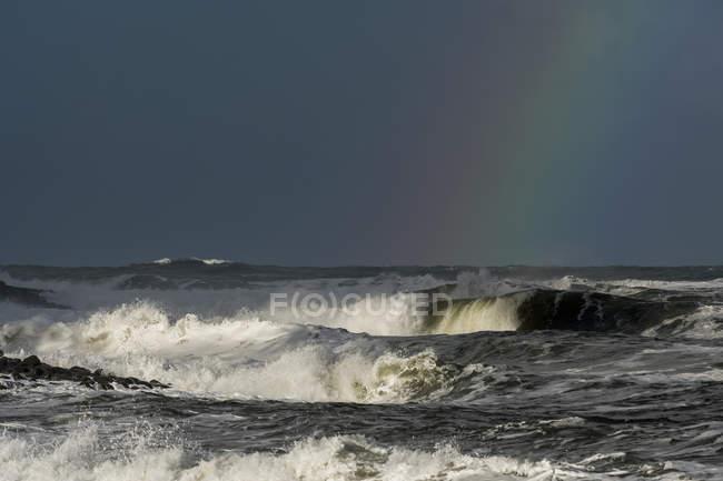 Tempo tempestuoso traz drama para o céu na Costa do Oregon com um arco-íris de cor contra a nuvem escura sobre as ondas; Litoral, Oregon, Estados Unidos da América — Fotografia de Stock
