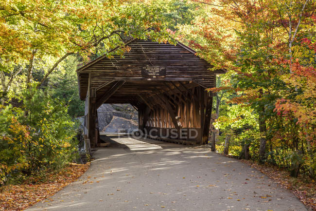 A covered bridge on a back country road in autumn, White Mountains National Forest; New England, United States of America — Stock Photo