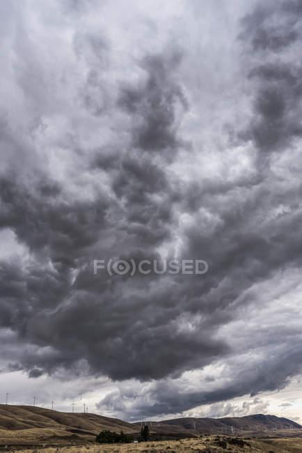 Dunkle Wolken Webstuhl mit Windkraftanlagen auf den Hügeln über Klickitat County; Maryhill, Washington, Vereinigte Staaten von Amerika — Stockfoto