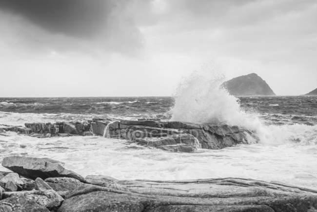Imagem em preto e branco de ondas salpicando contra rochas na costa ao longo da costa da Noruega — Fotografia de Stock
