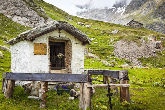 A small, historic shrine at Val Veni with Rifugio Elisabetta in the background, Alps; Aosta Valley, Italy — Stock Photo