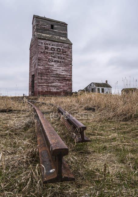 Ascensore a grano abbandonato con binari ferroviari arrugginiti nel Saskatchewan rurale; Saskatchewan, Canada — Foto stock