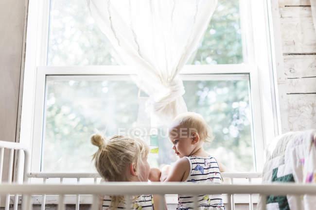 Due sorelle che giocano insieme nella culla dalla finestra — Foto stock