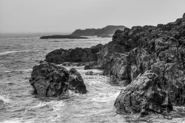 Schroffe Felsen säumen die Küste am Chesterman Beach mit Wolken und Nebel, die den Horizont verdunkeln, Pazifikrand, Vancouver-Insel; britische Columbia, Kanada — Stockfoto