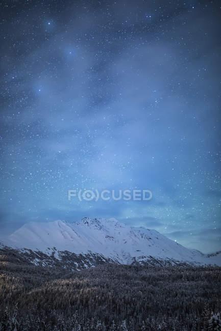 El débil resplandor de las auroras boreales en el cielo nocturno ilumina la nube dispersa en Moose Pass, Península de Kenai, Alaska meridional y central; Moose Pass, Alaska, Estados Unidos - foto de stock