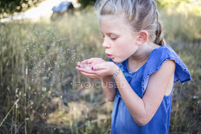 Young girl blowing a small grain from cupped hands into the air — Stock Photo