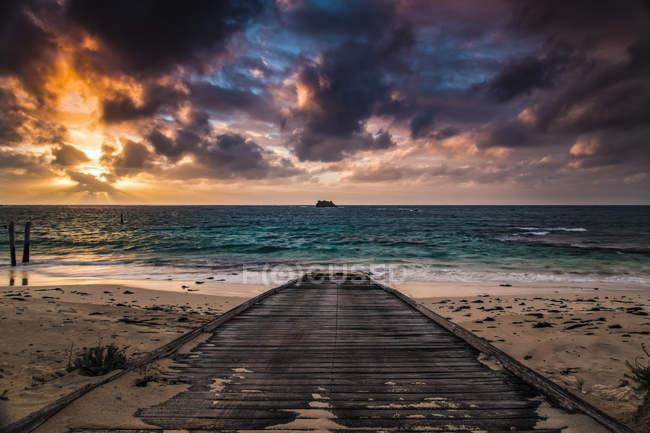 Деревянная набережная на пляже, ведущая к бирюзовой воде залива Хамелин на закате; Западная Австралия, Австралия — стоковое фото