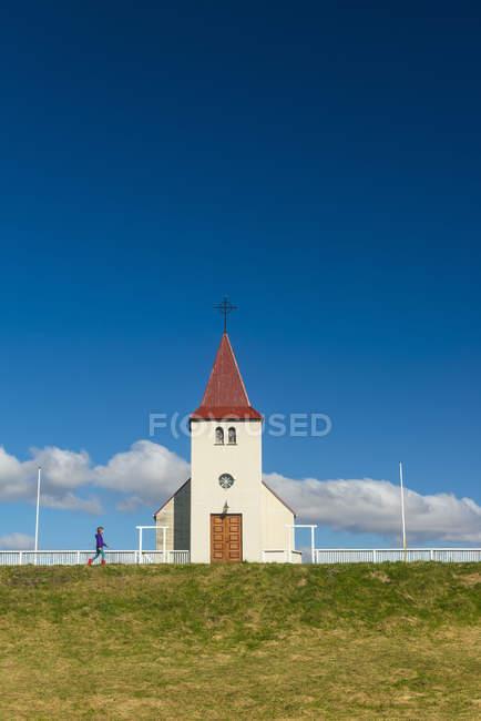 Chica caminando por la pequeña iglesia; Langaholt, Islandia - foto de stock