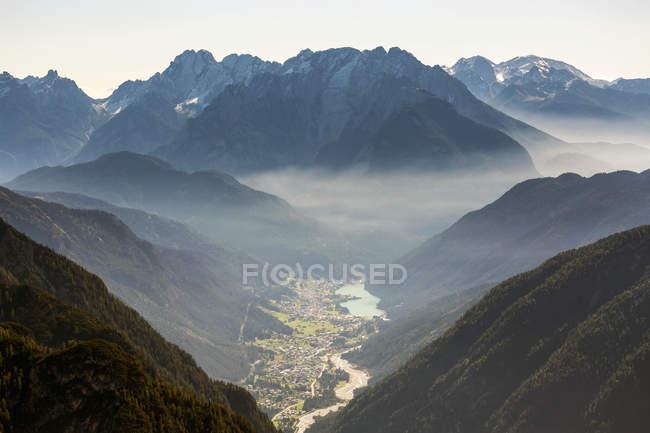 Sunrise with illuminated fog laying through the mountain range and over a valley; Sesto, Bolzano,Italy — Stock Photo