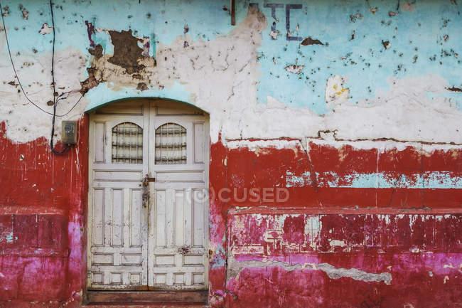 Fachada gastada y erosionada de un edificio con pintura descascarillada y puertas dobles; Nicaragua - foto de stock