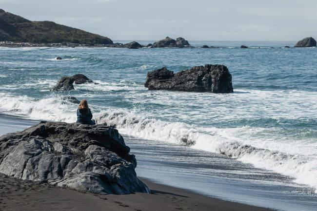 Женщина, размещения на скале на берегу, наблюдая волн, приходящих на берег вдоль скалистых берегов Калифорнии, Калифорния, США — стоковое фото