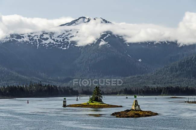 Vista desde Alaska estado Ferry de baja Wrangell Narrows hacia Isla de Wrangell, numerosos marcadores de navegación visibles y Zarembo Island visible en el fondo; Alaska, Estados Unidos de América - foto de stock
