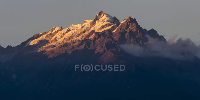 Sunlight illuminating the rugged peaks of the Kangchenjunga Mountain Range, a part of the Great Himalaya Range; Sikkim, India — Stock Photo