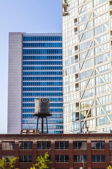 Edifícios no centro de Chicago com um reservatório de água no telhado de um edifício residencial, mostrando o contraste de velhos e novos edifícios; Chicago, Illinois, Estados Unidos da América — Fotografia de Stock