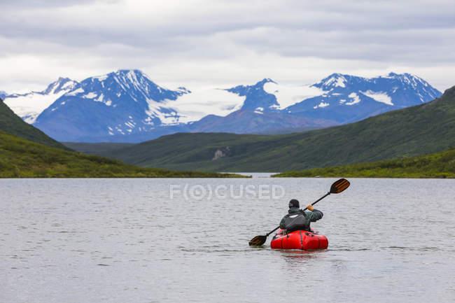 Mann paddelt mit Packfloß über Grenzstein Gap Lake, Alaska, USA — Stockfoto