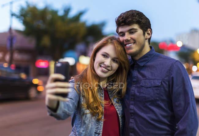 Commandes de jeune couple à la ville de rue au crépuscule et en prenant un selfie — Photo de stock