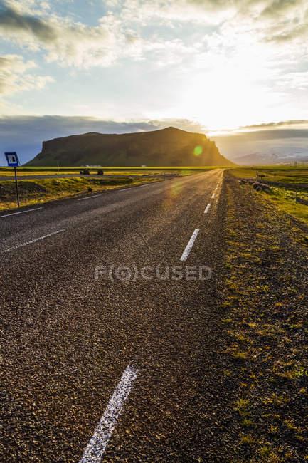 Сонце сідає за пагорби з шосе асфальтованої дорозі, що веде на захід сонця, Ісландія — стокове фото