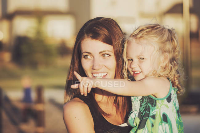 Little caucasian girl pointing on something while sitting on mother hands — Stock Photo
