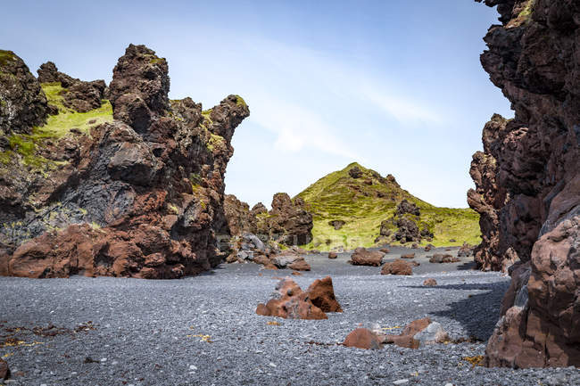 Colourful lava rock formations scattered across the black sand beach in Snaefellsjokull National Park, Iceland — Stock Photo