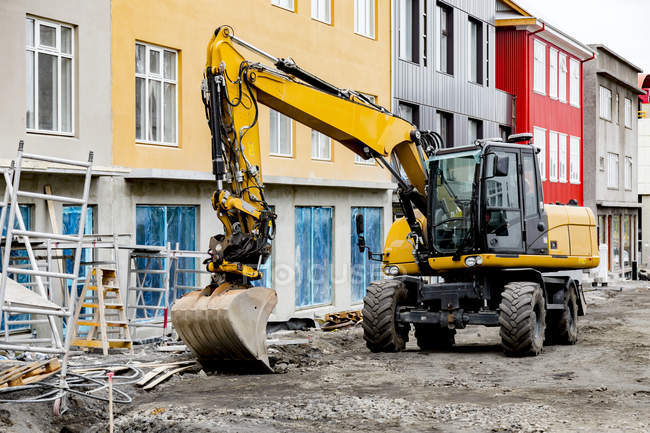 Large wheel loader in front of colorful buildings — Stock Photo