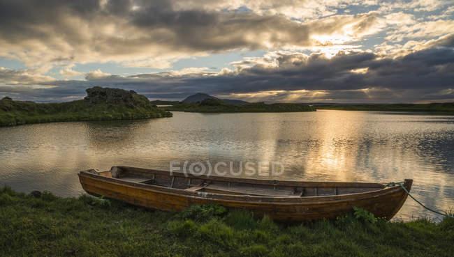 Um barco encontra-se em um Plácido Lago Myvatn, North Iceland ao pôr do sol; Islândia — Fotografia de Stock