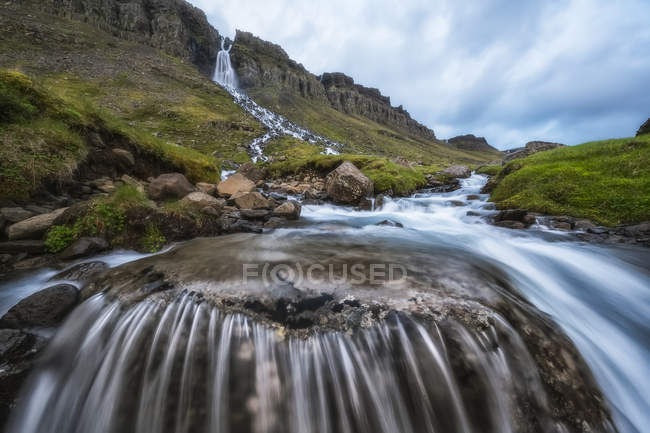 Motion blur of flowing water at a waterfall near Djupavik; West Fjords, Iceland — Stock Photo