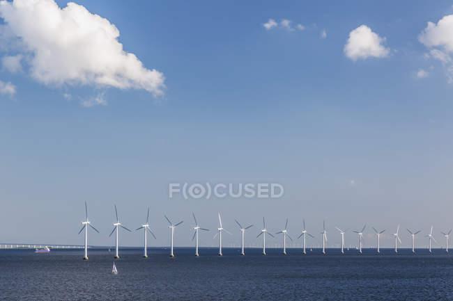 Небольшой парусник и ряда ветряных турбин в Балтийском море, производство электроэнергии от побережья Дании; Дания — стоковое фото