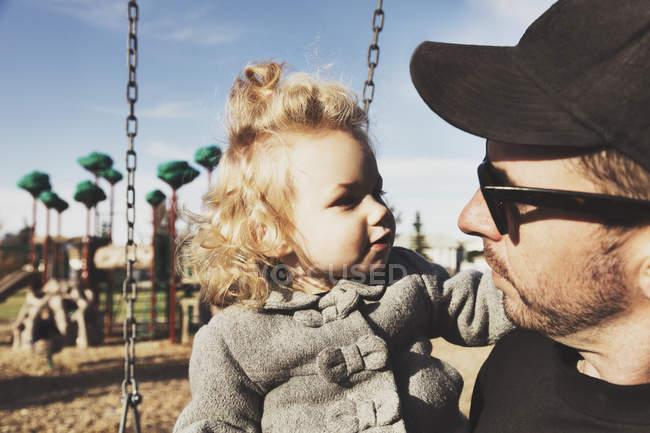 Linda chica joven con padre después de jugar en un parque infantil - foto de stock