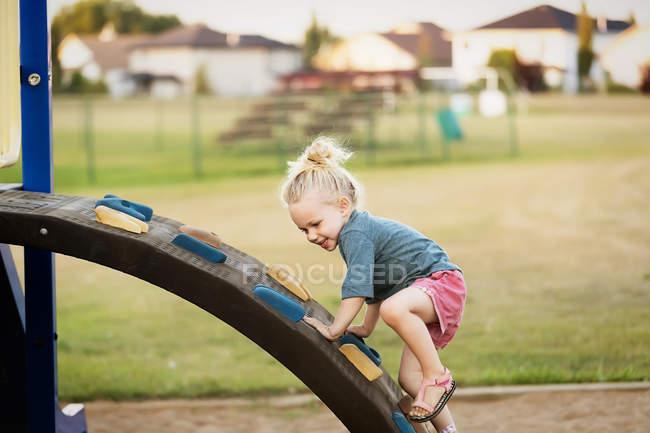 Junges Mädchen mit blonden Haaren spielt auf einem Spielplatz und klettert auf eine Felsleiter — Stockfoto