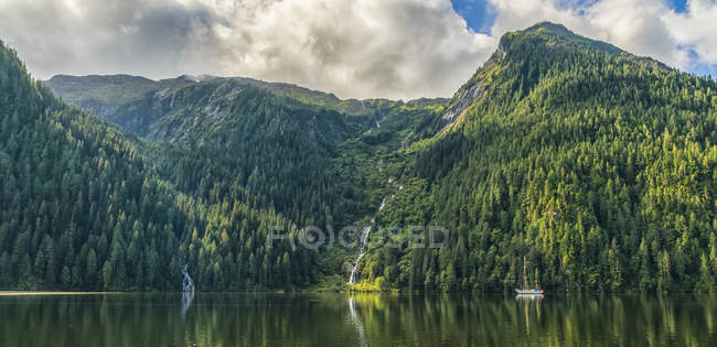Scenic view of the Great Bear Rainforest area with a sailboat on the water; Hartley Bay, British Columbia, Canada — Stock Photo