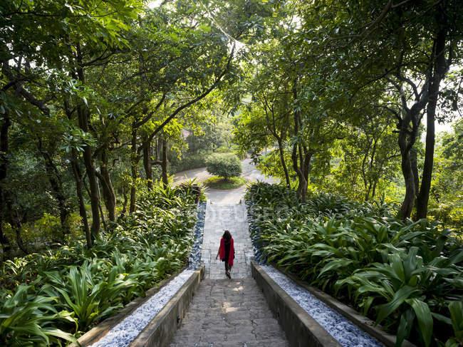Donna che cammina giù per le scale circondate da vegetazione lussureggiante, Ananda Hotel e Spa, Uttarakhand, India — Foto stock