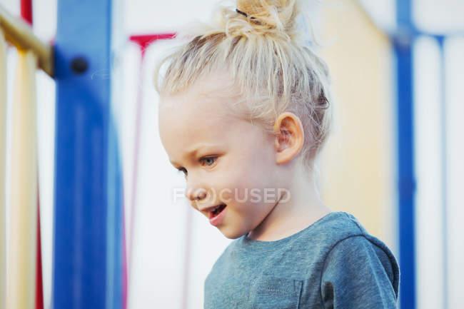 Крупный план молодой девушки с светлыми волосами, играющей на детской площадке — стоковое фото