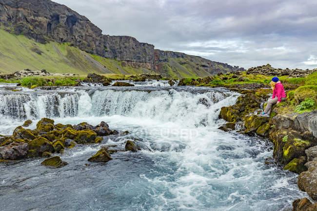Женщина-туристка позирует для фотографии на краю водопада; Исландия — стоковое фото