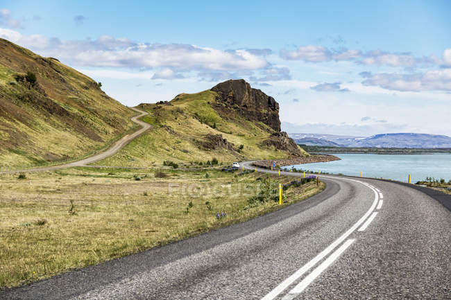 Long winding road leading into the hills in Iceland where open paved roads lead throughout the volcanic landscape to views across the country, Iceland — Stock Photo