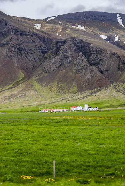 Large farmhouse estate property surrounded by vast fields in front of volcanic hillsides, Iceland — Stock Photo