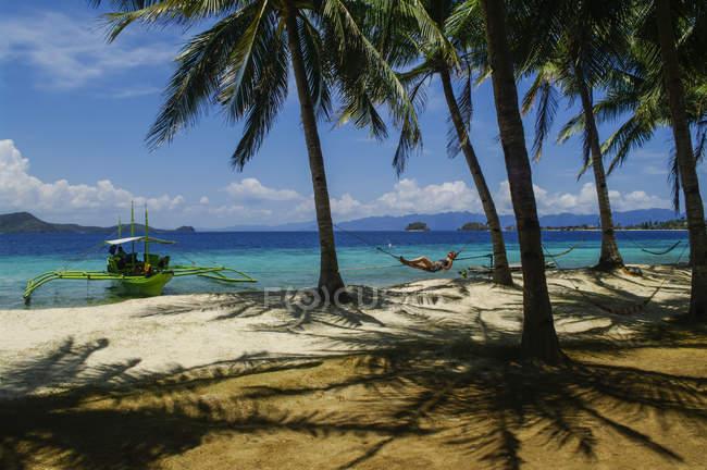 Жінка покладення гамаку на тропічному пляжі, аутригерами каное пришвартований уздовж берега, Андаманські, Сполучені Штати Америки — стокове фото