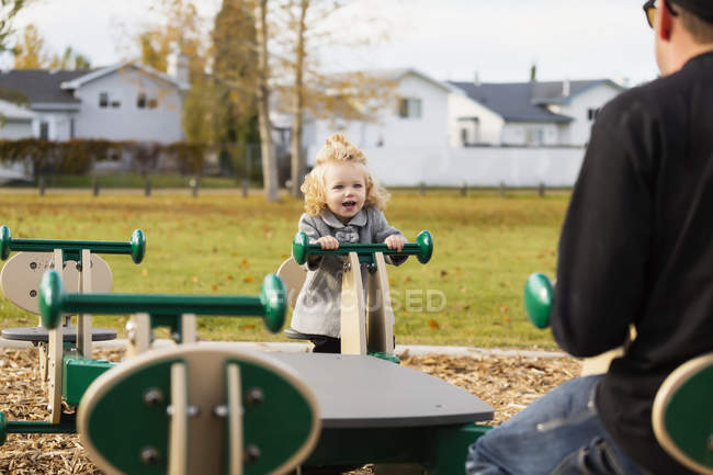 Cute young girl playing on seesaw with dad in playground — Stock Photo