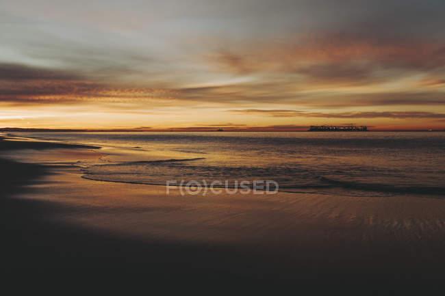 Закат моет золото и оранжевый на океан и пляж, Лонг Бич, Калифорния, Соединенные Штаты Америки — стоковое фото