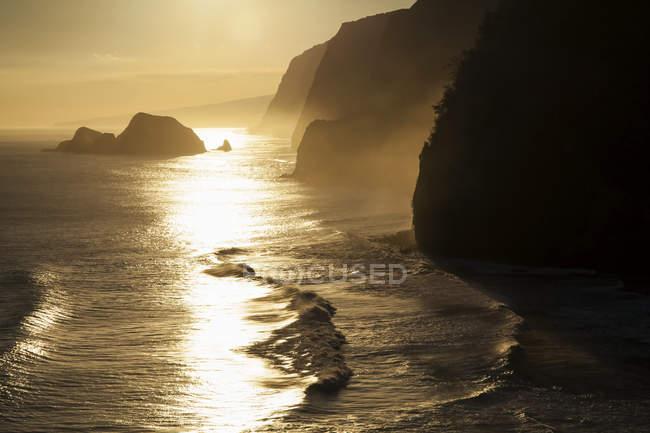 Salida del sol sobre la costa de Hamakua vista desde un mirador del sendero, Valle de Pololu, Kohala del norte; Isla de Hawai, Hawai, Estados Unidos - foto de stock