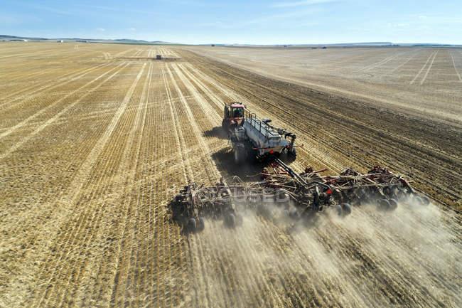Трактор, потянув воздуха сеялка, посевные поля с голубым небом на расстоянии — стоковое фото