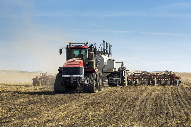 Tractor pulling an air seeder, seeding a field with blue sky and clouds in the background — Stock Photo