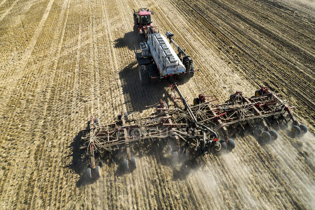 Aerial view of a tractor pulling an air seeder, seeding a field — Stock Photo