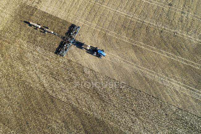 Vista aerea di un trattore che tira un air seeder, seminando un campo — Foto stock