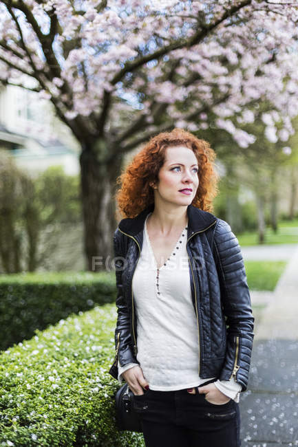 Retrato de uma mulher com cabelos vermelhos e encaracolados andando ao ar livre na primavera — Fotografia de Stock
