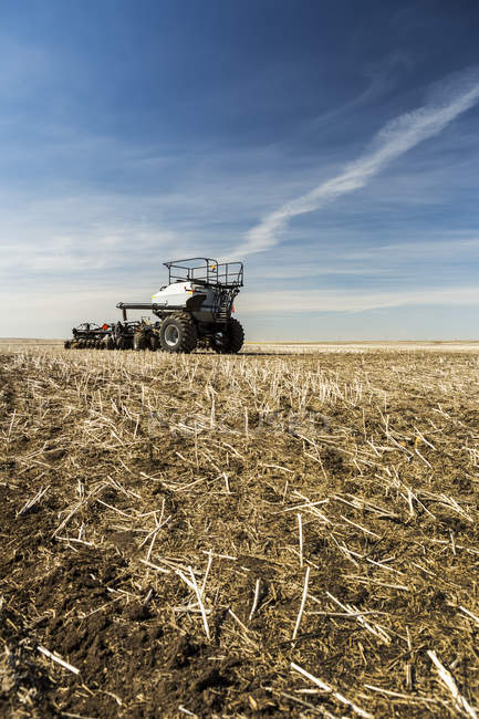 Hopper and air seeder in a canola stubble field with blue sky and clouds — Stock Photo