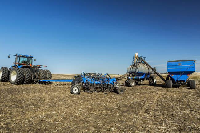 Работа с тяжелой техники в поле фермера — стоковое фото