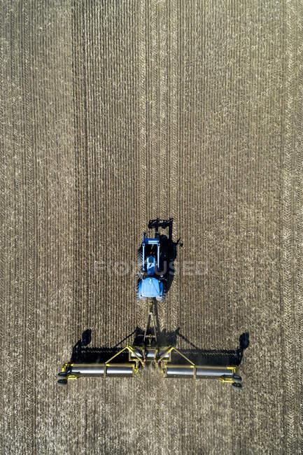 Vista aerea di un trattore tirando rulli per appiattire un campo — Foto stock