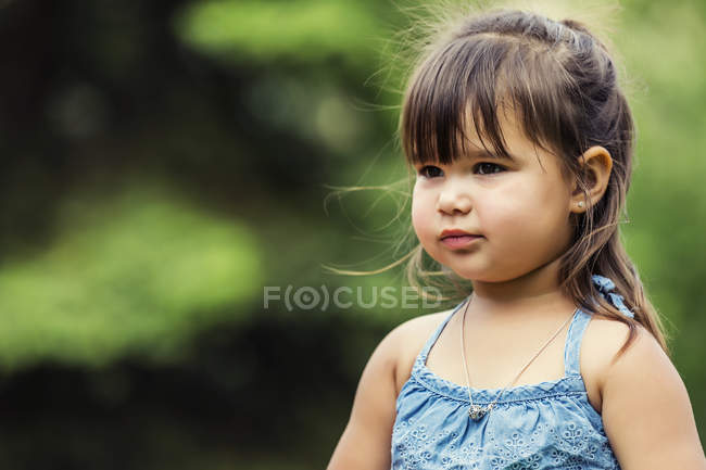 Portrait of a beautiful preschooler girl looking away against blurred green background — Stock Photo